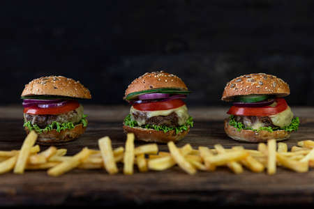 Hamburgers with tomatoes, onions, cucumber, lettuce , melting cheese and french fries served on a  rustic wooden table