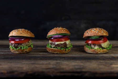 Hamburgers with tomatoes, onions, cucumber, lettuce and melting cheese served on a rustic wooden table