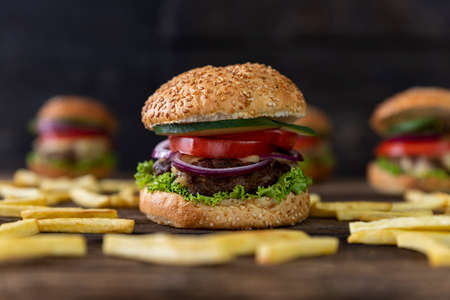 Hamburger with tomatoes, onions, cucumber, lettuce , melting cheese and french fries served on a  rustic wooden table