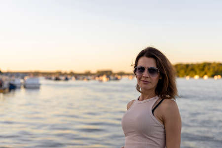 Beautiful woman wearing sunglasses at sunset by the river. Focus on the sunglasses