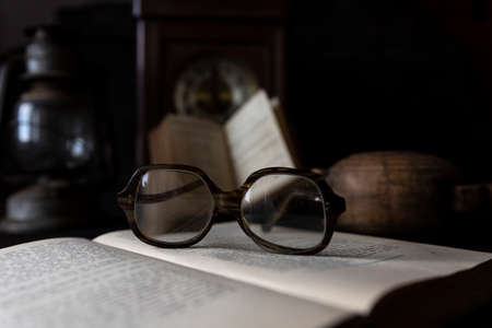 Old worn Glasses resting on an opened book with books and clock in background. Reading time concept Stock Photo