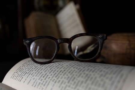 Old worn Glasses resting on an opened book with books and clock in background. Reading time concept