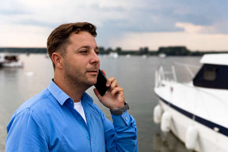 Man talking on the phone beside luxury yacht at port. Nautical and marine concept Stockfoto