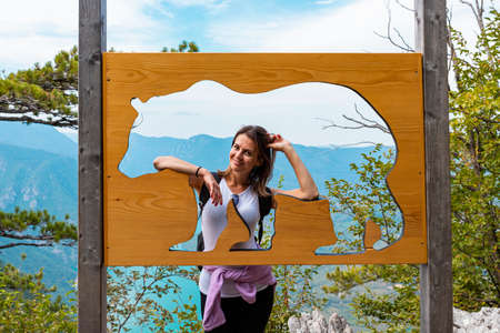 Woman hiker at mountain forest posing beside bear sign at natural reserve