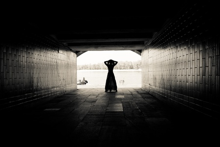 Silhouette of a girl on bright background at the end of an underground pedestrian tunnel Stock Photo - 18530330