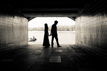tunnel view: Silhouette of a couple on bright background at the end of an underground pedestrian tunnel