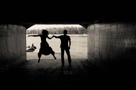 Silhouette of a couple on bright background at the end of an underground pedestrian tunnel Stock Photo - 18530325