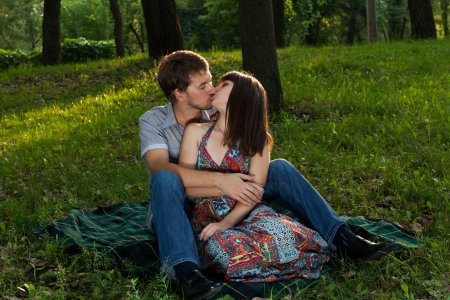 Young couple kissing on a romantic picnic in a park on a sunny day outdoors photo