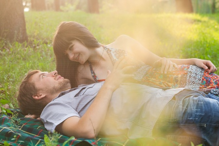 Young couple on a romantic picnic in a park on a sunny day outdoors photo