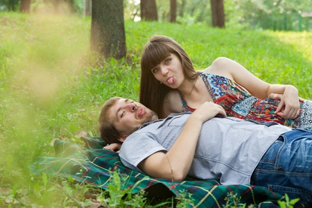 Young couple showing their tongues to photographer on a sunny day outdoors photo