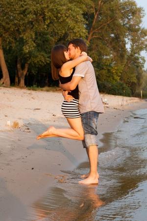 Jovem casal se abra�ando e se beijando no beira-rio ao p�r do sol Banco de Imagens - 18530470