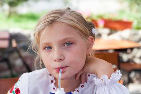 sipping: Young girl  posing in an outdoor cafe and sipping juice with a straw Stock Photo