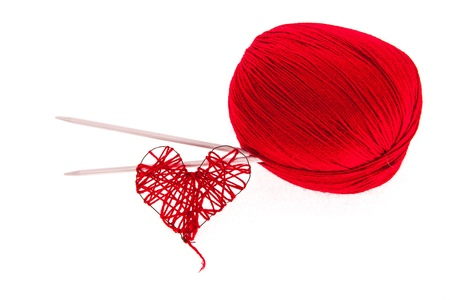 Red knitting yarn with needles and a heart isolated on white Stock Photo - 18530297