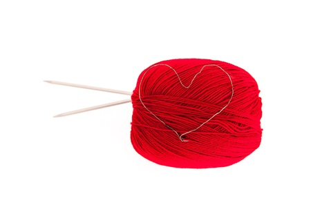 Red knitting yarn with needles and a heart isolated on white photo