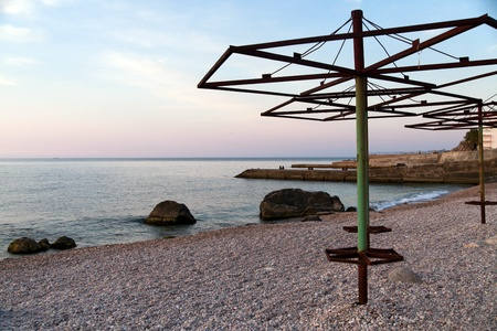 Dawn at pebble beach with old rusty umbrellas photo