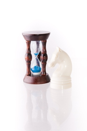 decisionmaking: White chess horse with sand-clock isolated on white