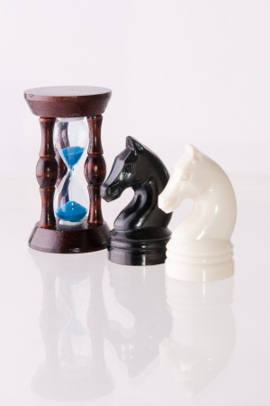 decisionmaking: Black and white chess horses with sand-clock isolated on white