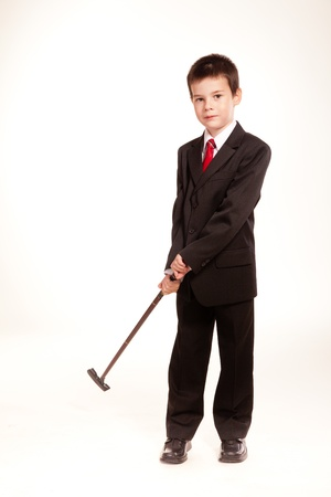 Young boy posing in studio in a black suit and a red tie, business code, isolated on white photo