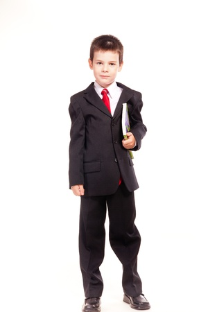 Young boy posing in studio in a dark suit and a red tie holding a book, business dress code, isolated on white photo