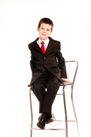 Young boy posing in studio in a dark suit and a red tie sitting on a chair and talking on mobile phone, business dress code, isolated on white photo
