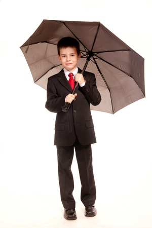 drizzling rain: Young boy posing in studio in a dark suit and a red tie with an umbrella, business dress code, isolated on white