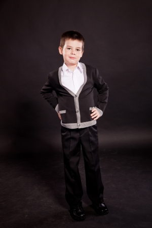 drizzling rain: Young boy posing in studio in a dark suit and a red tie with an umbrella, business dress code, on black in studio