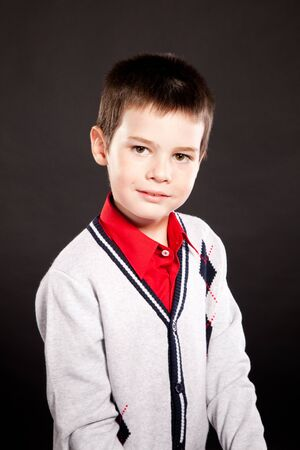 dresscode: Young boy posing in studio in stylish business dresscode, on black