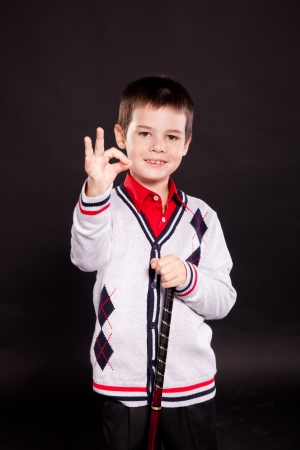 Young boy posing in studio in stylish business dresscode, on black photo