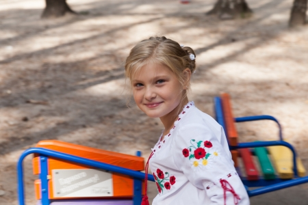 Pre-teenage girl in Ukrainian style shirt on a swing photo