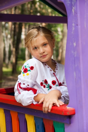 Pre-teenage girl in Ukrainian style shirt on child rides photo