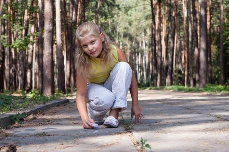 Young girl model is drawing on the concrete ground with chalk in a forest park photo