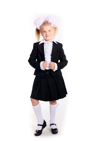 Young girl in school uniform with a jacket and ponytales posing in studio on white photo