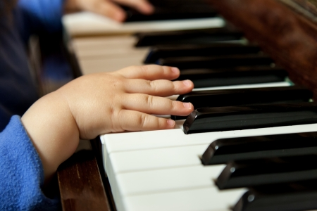 Baby hands playing classic piano photo