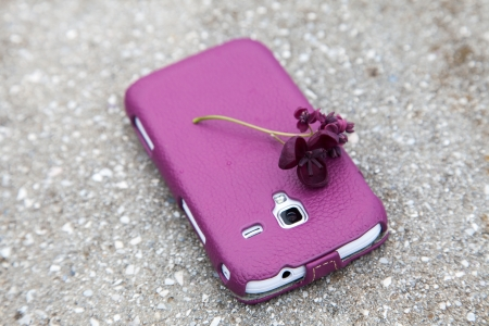 White cell phone in a case with a matching color flower photo