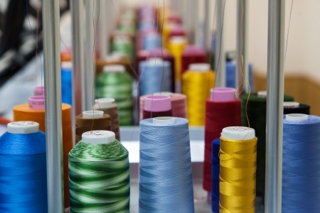 Colorful reels of threads background - interior of industrial textile factory Standard-Bild