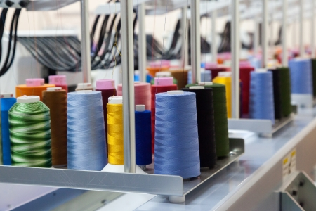 industrial objects equipment: Colorful reels of threads background - interior of industrial textile factory Stock Photo