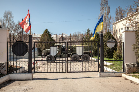 overtaken: BELBEK, UKRAINE - March 21, 2014 Blocked entrance gate to the Ukrainian military base A4515 before being overtaken by Russian occupants