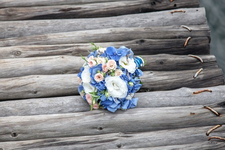 bridge over water: Bridal bouquet laying on wooden bridge over water
