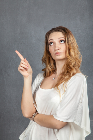 Young woman showing disapproval with finger pointing in studio