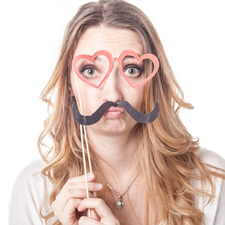Young woman with mustache playing various emotions in studio, emoticons photo
