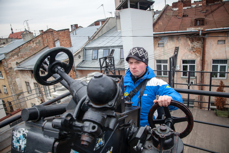 peaking: LVIV, UKRAINE - February 23, 2015 Machine gun on Kryiivka pub roof with photographer peaking Editorial
