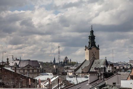 old town guildhall: High church tower among old roofs Lviv Ukraine