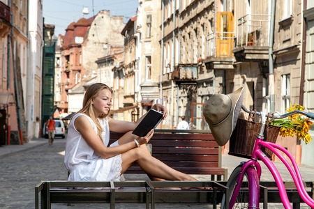 grocery basket: girl with pink bicycle and grocery basket sitting on street bench and reading book