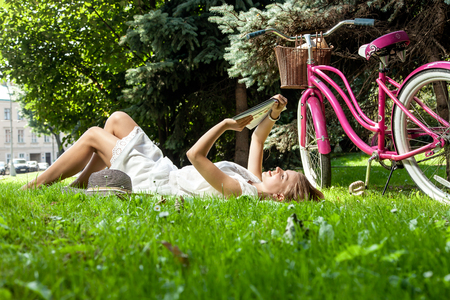 Attractive woman lays on green grass reading book in city park with pink bicycle behind her