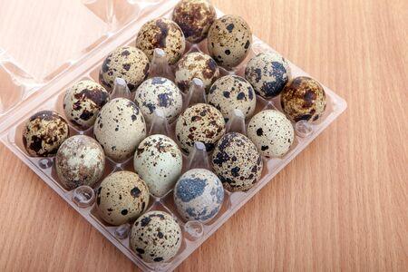 huevos de codorniz: huevos de codorniz en un recipiente de pl�stico transparente en la mesa de cocina de madera