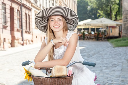 erudition: women on pink bicycle with grocery basket posing in street on sunny day