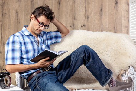 lounge: man relaxing on sofa couch reading literature novel story book at home living room lounge