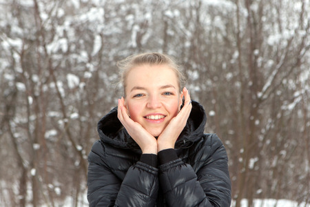 portrait of cute young woman in snow park in winter Stock Photo