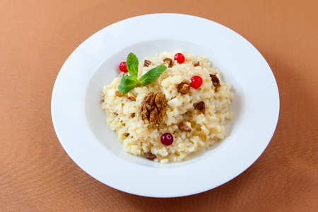 epicure: Fancy decorated oatmeal porridge with nuts and berries for healthy breakfast