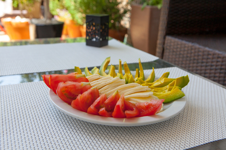 Summer healthy snack: avocado, cheese, bread, tomatos, watermelon served on outdoor porch table Stock Photo
